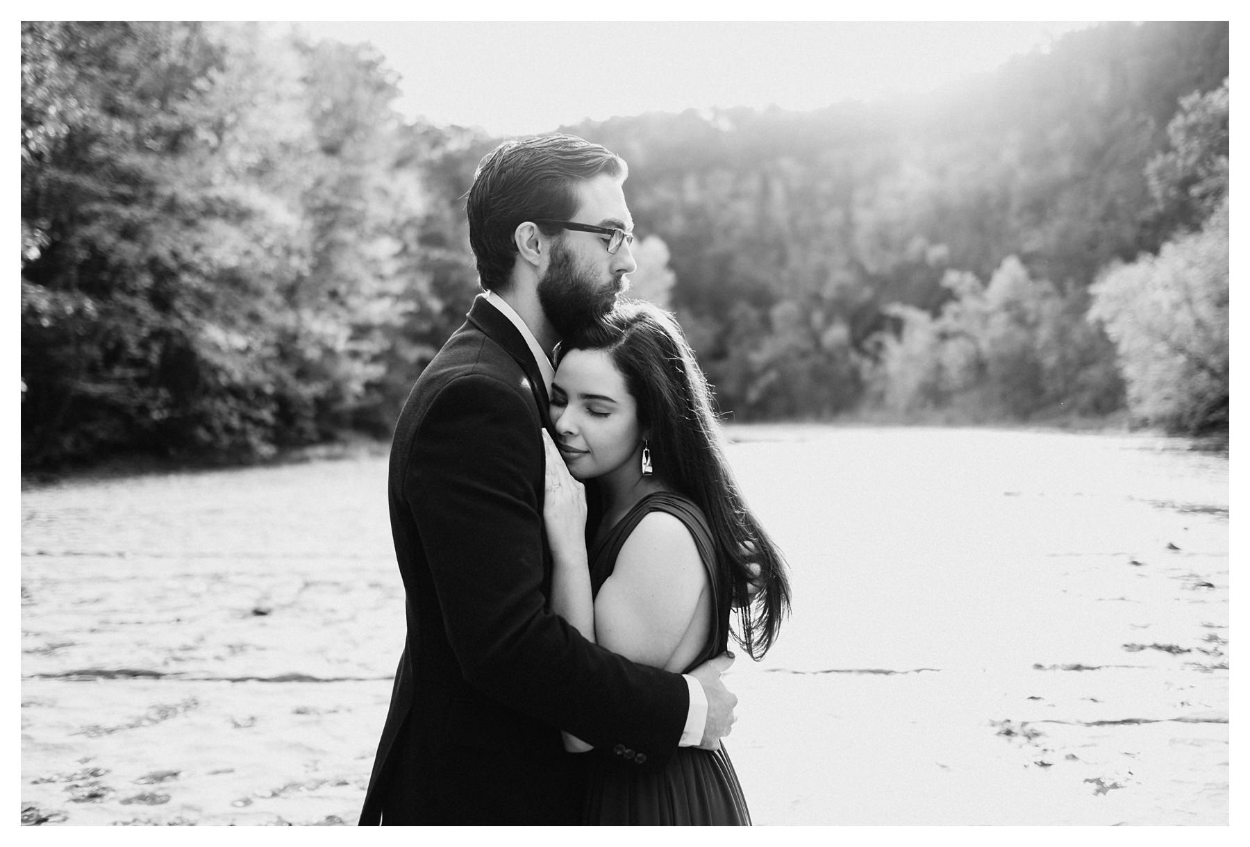 taughannock falls engagement session couple hugging black and white