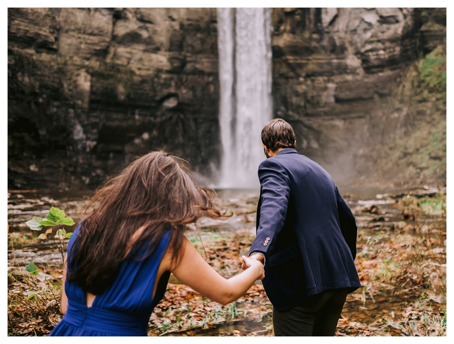 taughannock falls engagement session walking towards waterfall