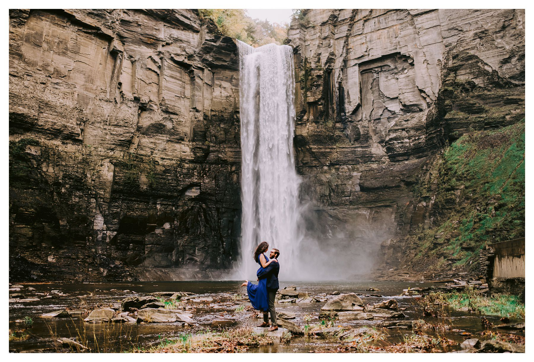 lifting bride up at taughannock falls engagement session in front of waterfall