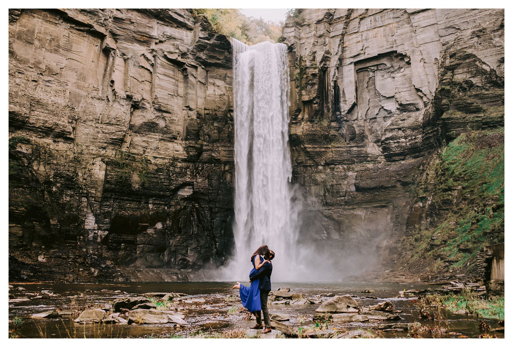 kissing in air taughannock falls engagement session in front of waterfall